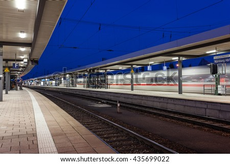 Modern railway station with high speed passenger train on railroad track in motion. Railway platform at night  in Nuremberg, Germany. Fast train. - stock photo