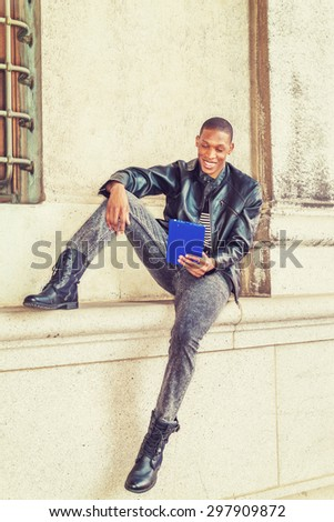 Modern Reading. Wearing black leather jacket, striped undershirt, jeans, boots, hand holding tablet computer, an African American guy sitting against wall on street in New York, smiling, reading.