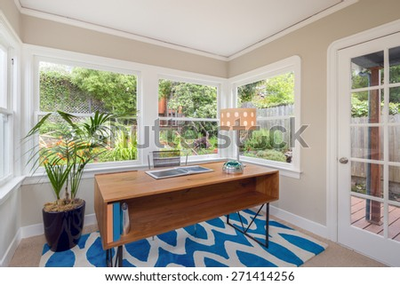 Modern rectangle wooden desk and table lamp in glass house style home office surrounded by green garden. Work-space table standing on blue pattern rug and large grids glass door leading to outdoors. - stock photo