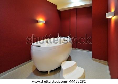 Modern red bathroom with hydro massage bathtub. - stock photo