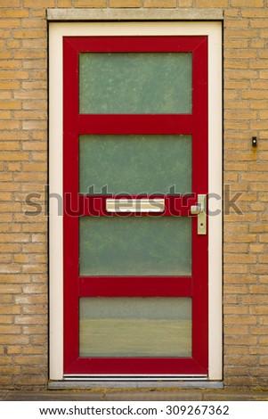 Modern red door with doorbell in brick wall - stock photo