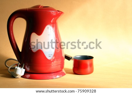 Modern red electric kettle and coffeepot standing on nice yellow background - stock photo