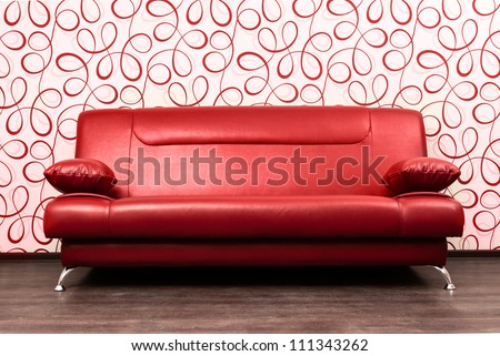 Modern red sofa in front of the wall with abstract wallpapers - stock photo