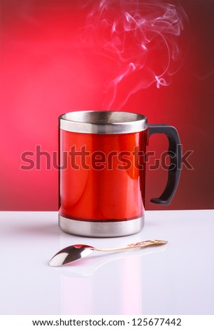Modern red travel mug with hot tea and spoon