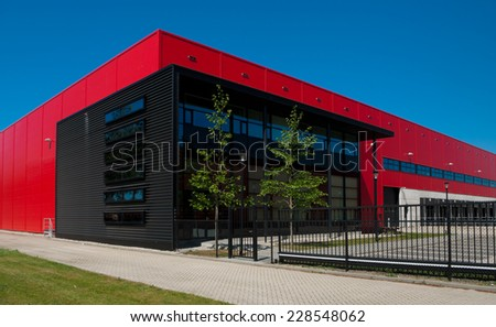 modern red warehouse in the Rotterdam harbor area - stock photo