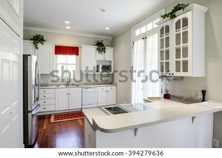 Modern residential kitchen with white cabinets and maple floors - stock photo