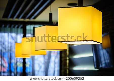 Modern restaurant interior with yellow square lamps - stock photo