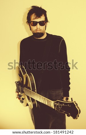 Modern Rock Guitarist. A male musician with a guitar loosely hanging from his shoulders, wearing sunglasses and looking into camera. Edited with an authentic vintage film look. - stock photo