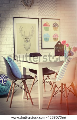Modern room interior with table, chairs and pictures on the wall - stock photo