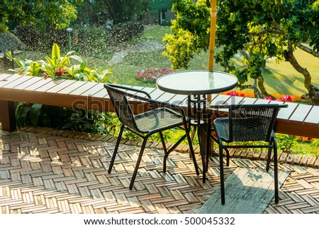 Modern round table and wicker chairs with sunshine. They are on a terrace or patio.
