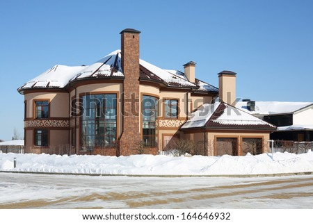 Modern rounded cottage with long chimneys at frosty and sunny winter day. - stock photo