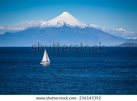 Modern sailboat sails in front of Osorno Volcano - stock photo