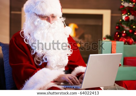 Modern Santa Claus sitting by fireplace using computer computer.?