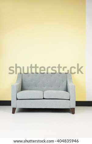 Modern Seafoam Green Couch Against a Pastel Yellow Wall - stock photo