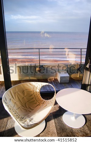 Modern seat and chairs overlooking the sea - stock photo