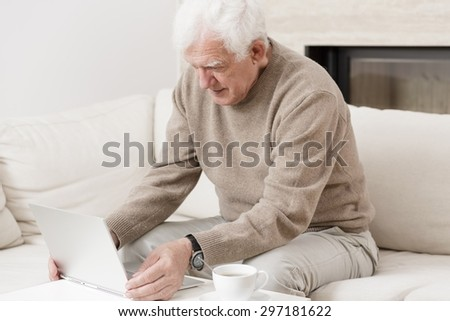 Modern senior man sitting on the sofa with laptop - stock photo