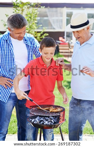 Modern senior man, young man and boy cooking barbecue  - stock photo