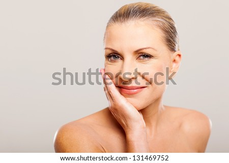 modern senior woman with hand on her face - stock photo