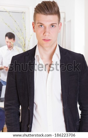 modern serious business man in suit standing wearing white shirt and black jacket with colleagues in background - stock photo