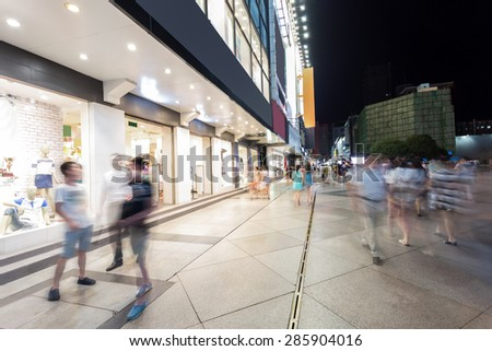 Modern shopping street and people in urban city with cement road at night   - stock photo