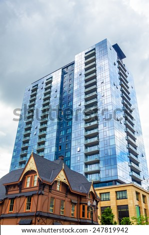 Modern skyscraper rising above a well kept old historic looking house in Portland, Oregon - stock photo
