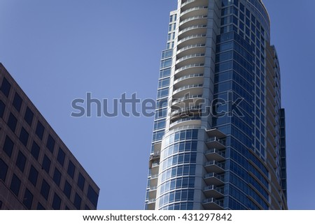 Modern skyscraper with glass facade against a clear blue sky - stock photo