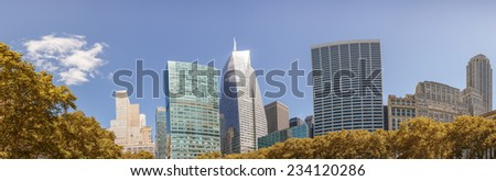 Modern skyscrapers surrounded by park trees under a beautiful blue sky. - stock photo