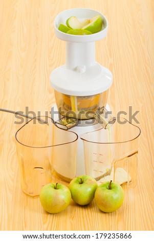 modern slow juicer making organic apple juice - stock photo