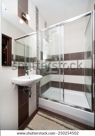 Modern small bathroom with sink and shower tiled with white and brown tiles