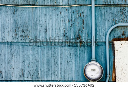 Modern smart grid residential digital power supply meter mounted on grungy blue exterior wooden wall - stock photo