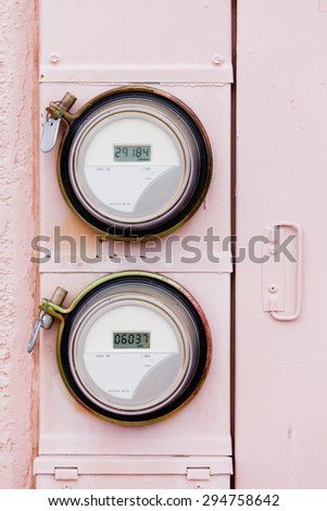 Modern smart grid residential digital power supply watthour meters on grungy pink exterior wall - stock photo