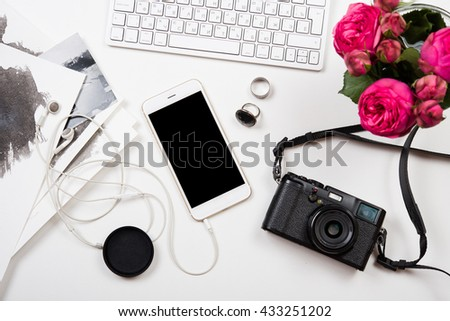 Modern smartphone, computer keyboard and photo camera on white t