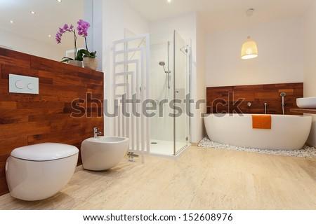 Modern spacious warm bathroom with sower and bath - stock photo