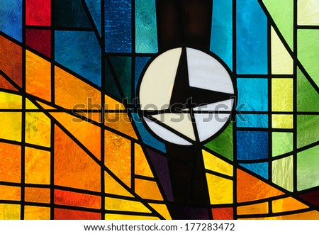Modern stained glass window with a clock within colorful abstract design, symbol of discernment and waiting for the inspiration of the Holy Spirit - stock photo