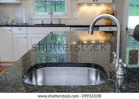 Modern stainless steel faucet and sink on kitchen island. Elegant granite counter. - stock photo