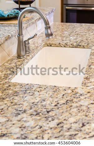 Modern Stainless Steel Faucet on Granite Kitchen Counter in New Home - stock photo