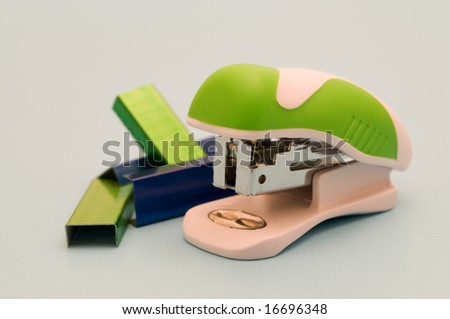 modern stapler on blue background - stock photo