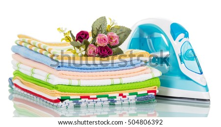 Modern steam iron and stack of towels, a rose isolated on a white background.