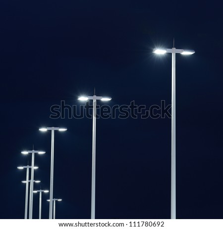 Modern street lights illuminated at night against a dark sky - stock photo
