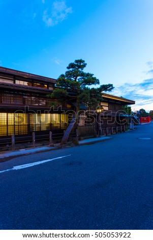 Modern street runs in front of traditional Japanese wooden house illuminated at twilight past Naka-bashi bridge in historic old district of Hida-Takayama in Gifu Prefecture, Japan. Vertical
