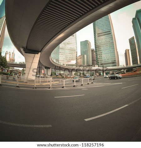 modern street scene under pedestrian bridge in shanghai downtown - stock photo