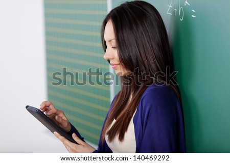 modern student working on digital pad with board in background - stock photo