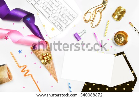 Modern style background, flat lay. Gold and party items: Cocktail tubes apple, pear, spiral, ice cream cone, gold cosmetic bag, scissors, paste. Desktop. view table, up. Open envelope.
