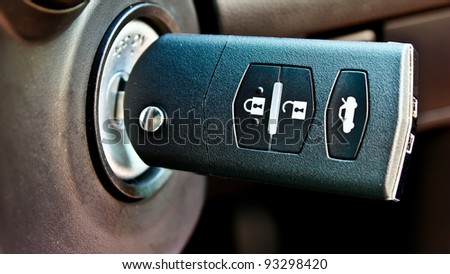 modern style car key on the key hole - stock photo