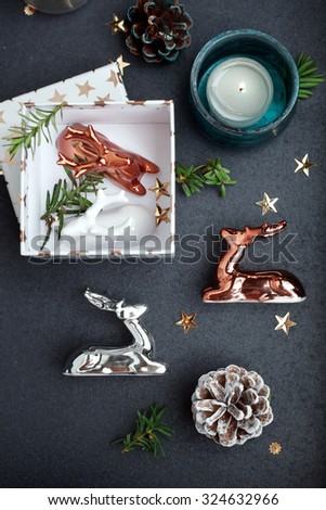 Modern style Christmas decor - ceramic reindeer in copper, silver and white colors, gift box and candles on coffee table. Natural light. Toned photo. Shallow focus. - stock photo