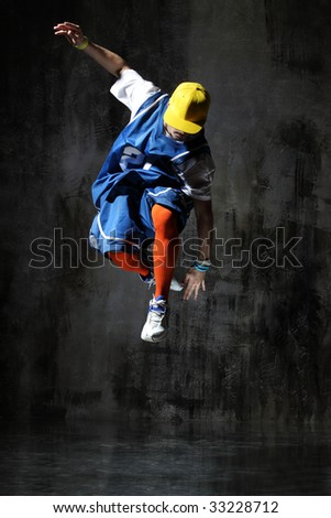 modern style dancer jumping on dirty grunge background - stock photo