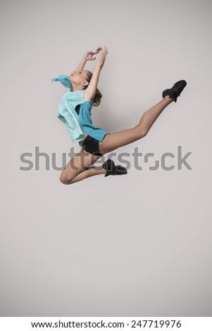 modern style dancer jumping on studio background - stock photo