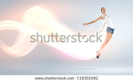 Modern style female dancer jumping and posing with lighting - stock photo