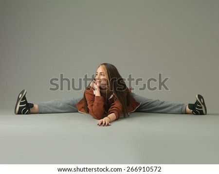 modern style female dancer performing a split on grey studio background - stock photo