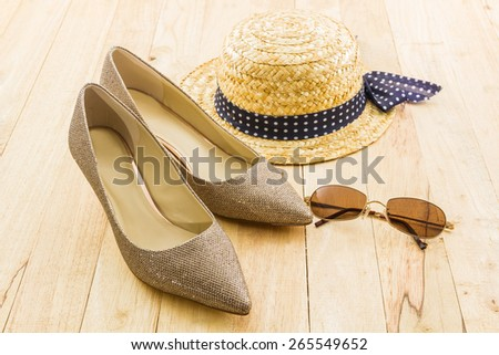 Modern style image of female fashion: straw hat, sun glasses and high heel of golden shoes on wooden background.   - stock photo